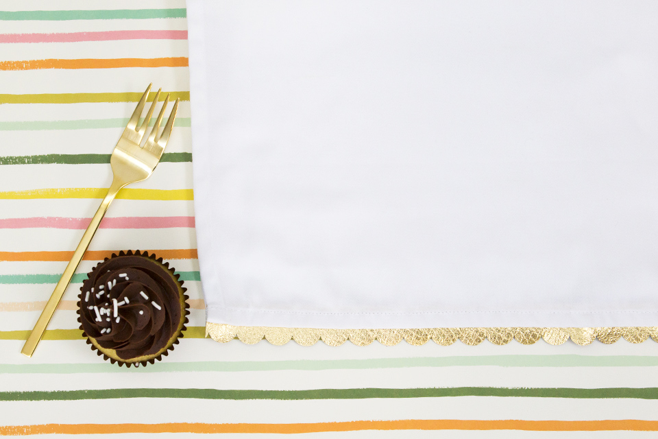 How cute are this gold scallop cloth napkin? The store bought napkin was transformed by sewing a strip of gold vinyl to the edge.